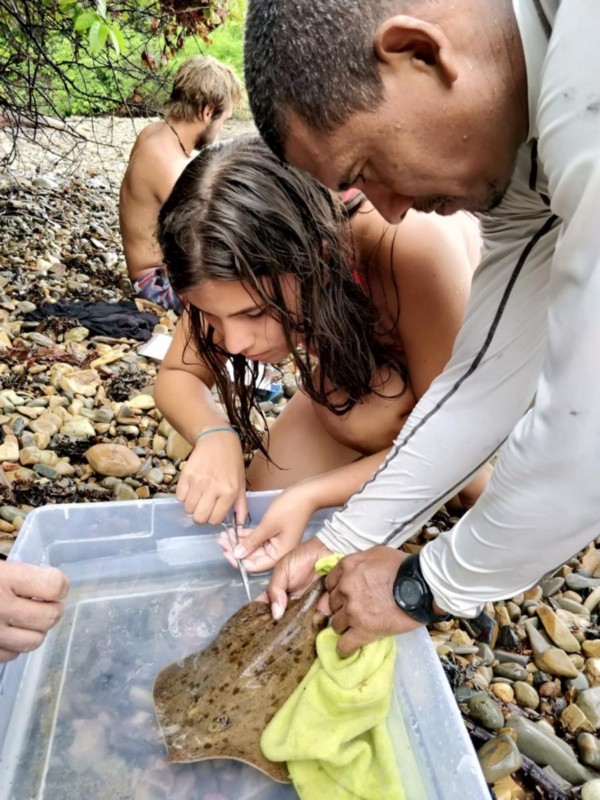 A young volunteer sampling a ray for health with an ETC researcher