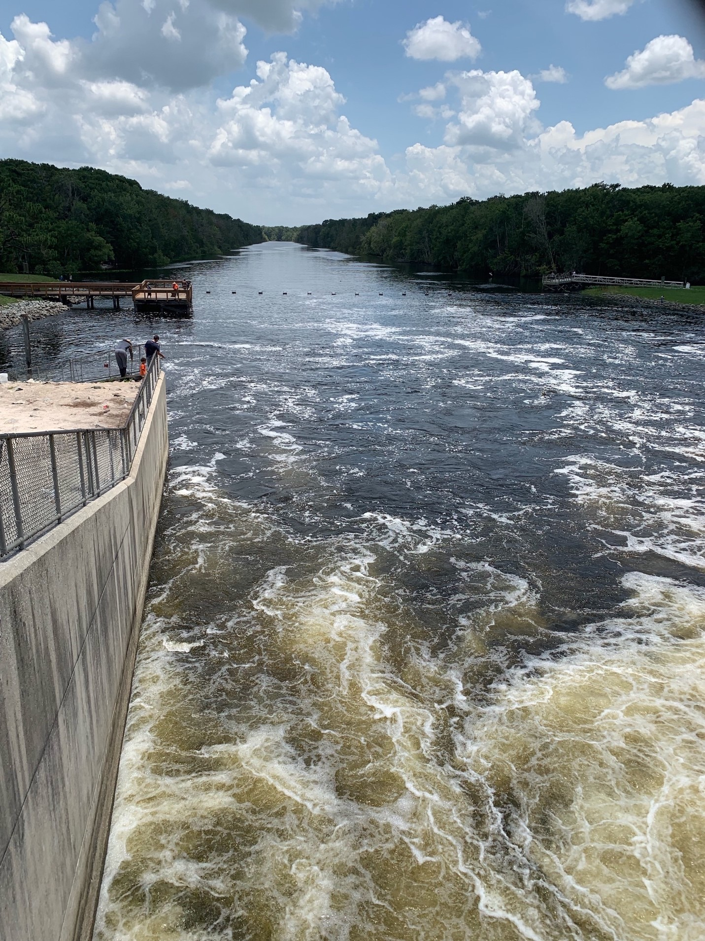 Churning water from the Rodman Reservoir enters the Ocklawaha River, where families fish from shore