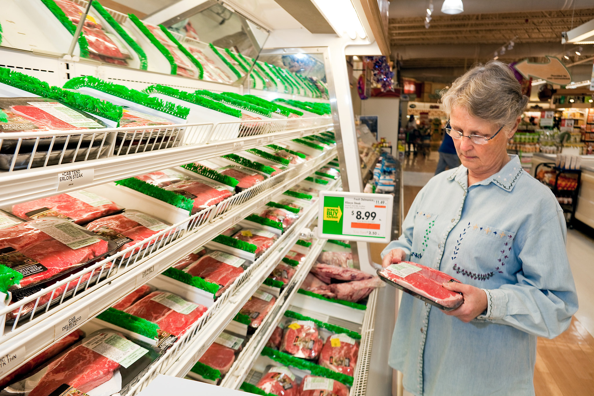A shopper examines a package of meat in a grocery store