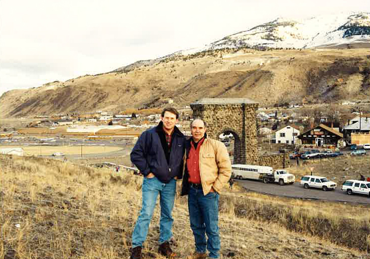Rodger Schlickeisen and volunteer posing with Yellowstone arch and trailer