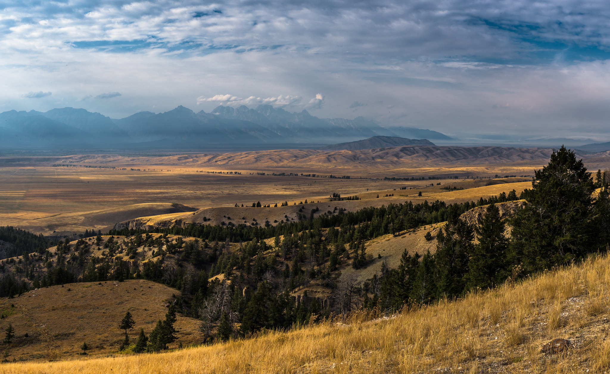 The Teton Range, partially obscured by smoke from the Berry Fire, rises beyond the Jackson Hole valley.