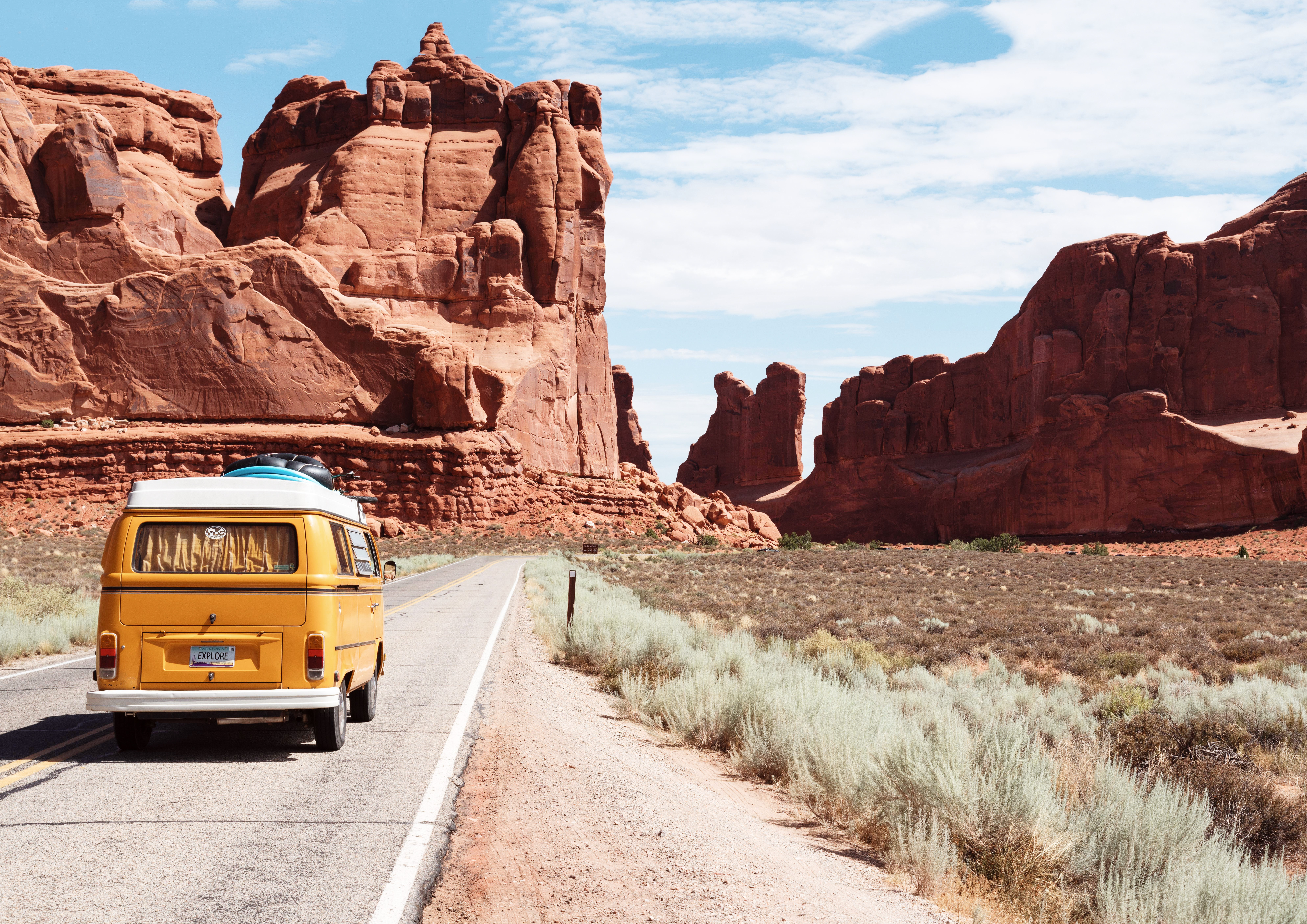 Yellow volkswagen bus on road in Arches NP