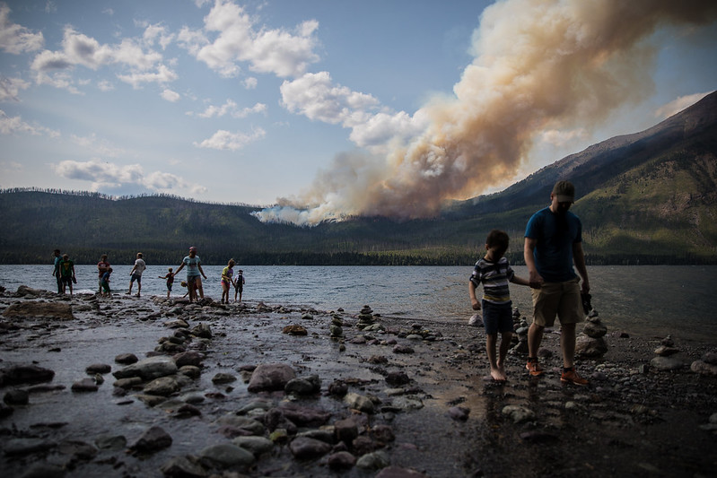 The Howe Ridge Fire from Lake McDonald Lodge with people walking around the lake edge
