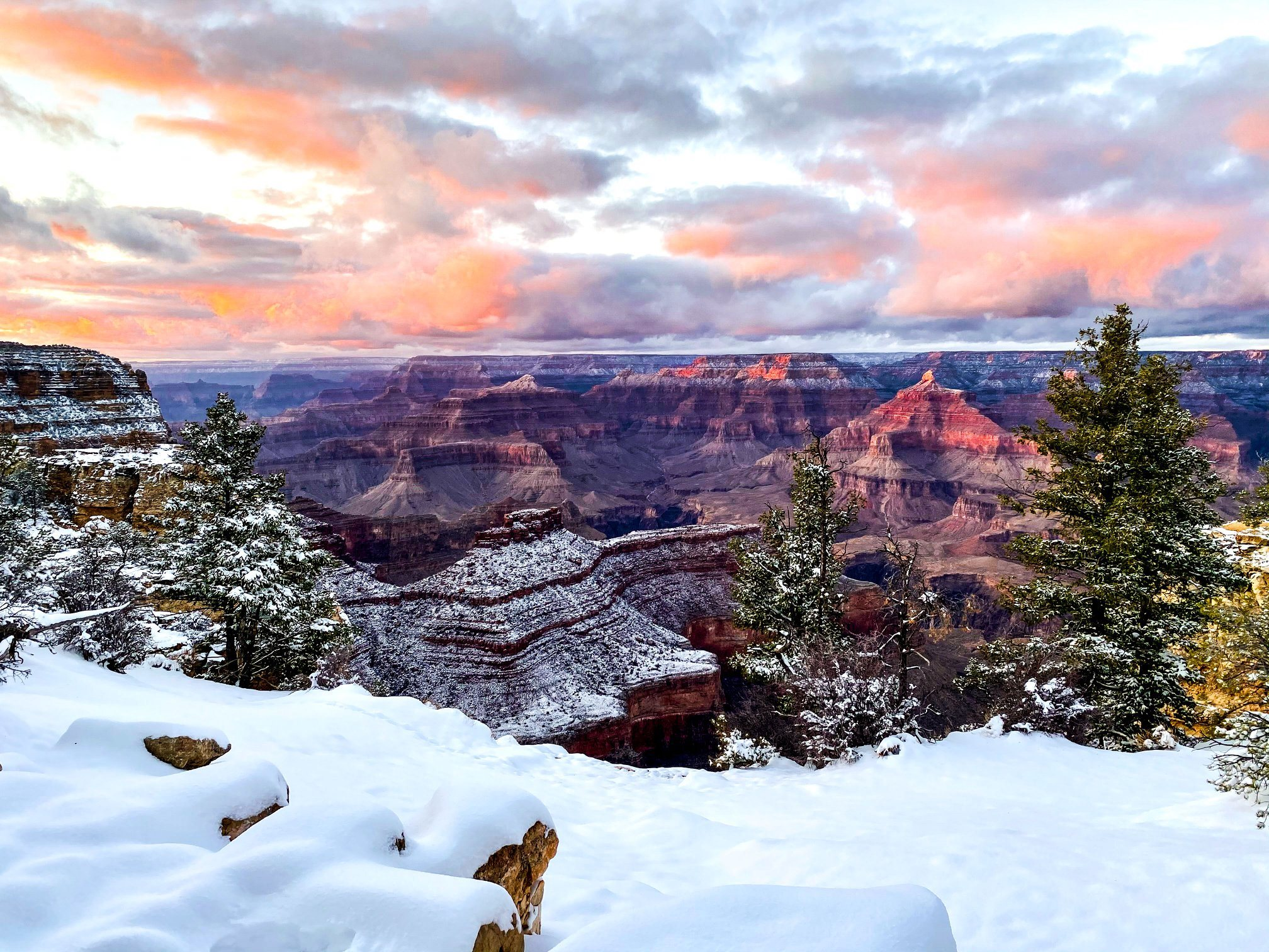 A pink sunset over the snow-covered rim of the Grand Canyon
