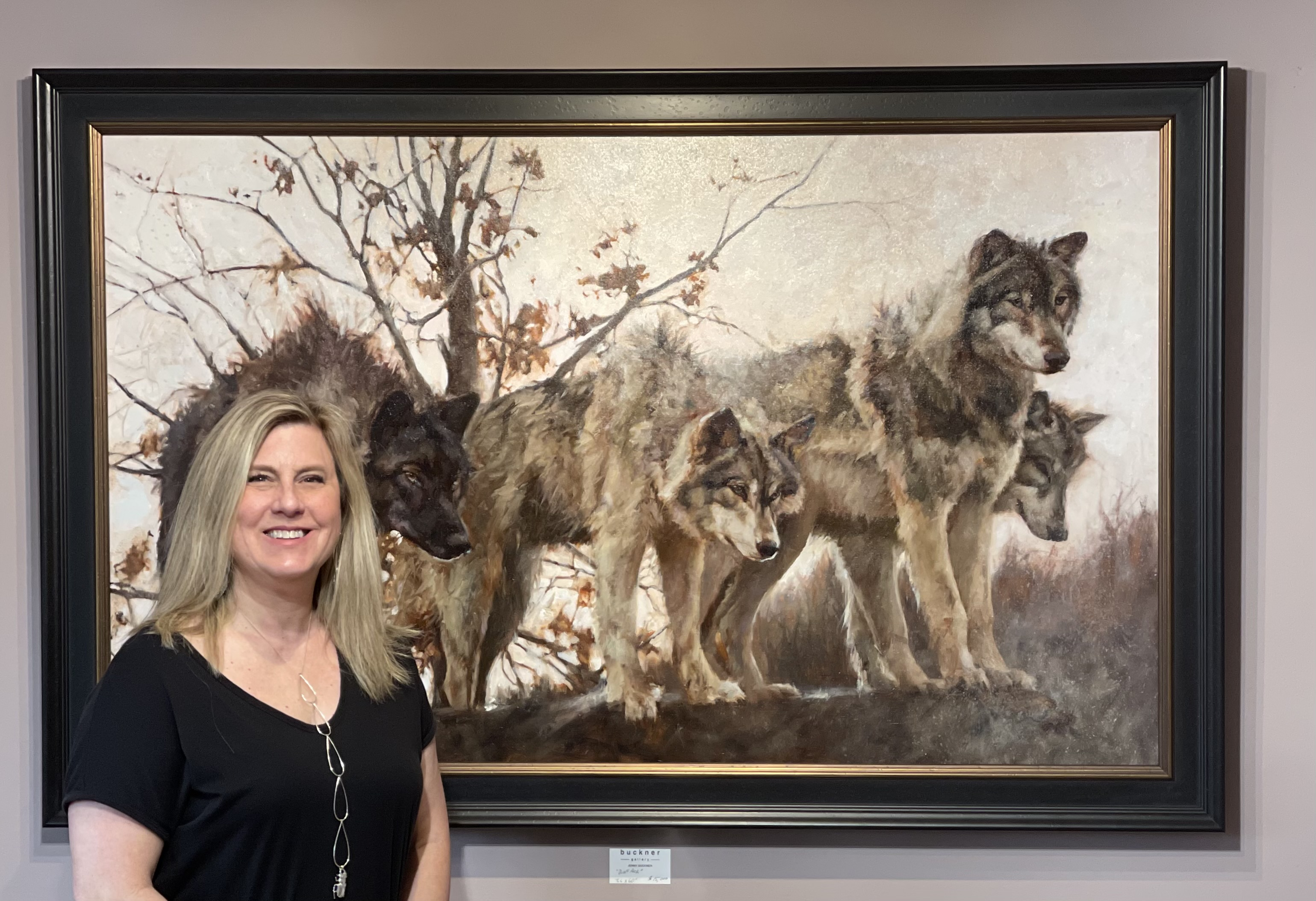 artist standing by wolf painting